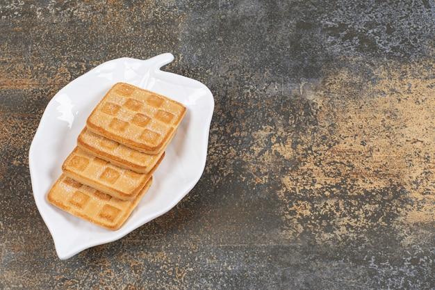 Kwadratowe słodkie krakersy na talerzu w kształcie liścia.