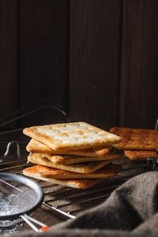 Kwadratowe suche krakersy herbatniki na drewnianym stole drewniane tekstury ciemne tło przekąska suche herbatniki