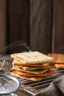 Kwadratowe suche krakersy herbatniki na drewnianym stole drewniane tekstury ciemne tło