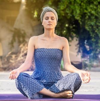 Kwadratowe zdjęcie młodej kobiety na zewnątrz. pozycja medytacyjna, oczy zamknięte i skrzyżowane nogi. ćwicz jogę