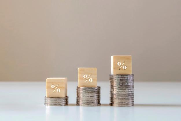 Kwadratowy drewniany klocek z ikoną procentu na stosie rosnących monet, koncepcji finansów i inwestycji.