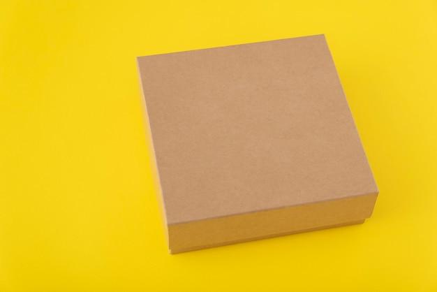 Kwadratowy karton na żółtym tle. skopiuj miejsce. makieta