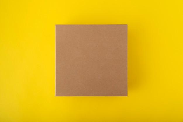 Kwadratowy karton na żółtym tle, widok z góry. pudełko rzemieślnicze bez etykiet.