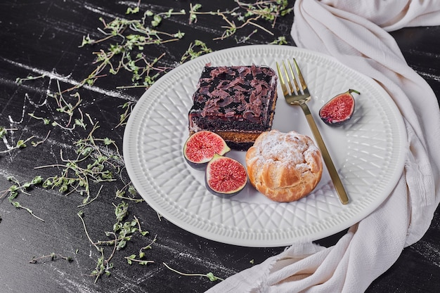 Kwadratowy kawałek sernika czekoladowego z figami i bułką.