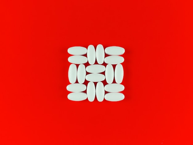 Kwadratowy kształt wykonany z białych tabletek na czerwonym tle.