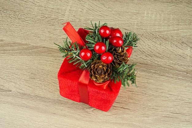 Kwadratowy prezent w opakowaniu i czerwone kokardki zielone świerkowe gałęzie