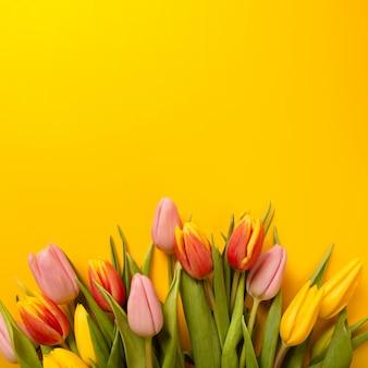 Kwadratowy tło z bukietem tulipany na żółtym tle. leżał z płaskim, widok z góry z lato.