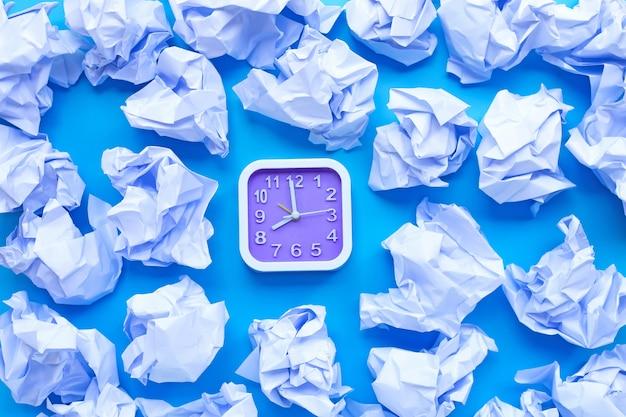 Kwadratowy zegar z białymi zmiętymi papierowymi piłkami na błękitnym tle.