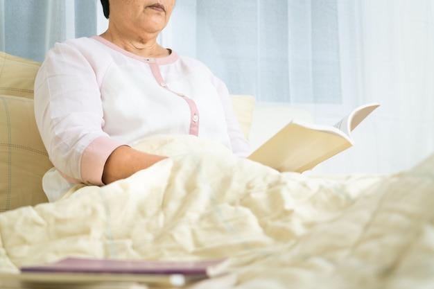 Kwarantanna covida-19 dla starszej kobiety czyta książkę, aby zostać w domu, aby uniknąć ryzyka