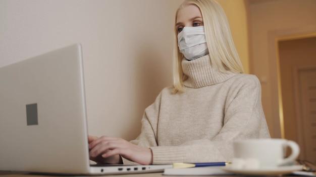 Kwarantanna. izolacja, dystans społeczny, niezależna praca w biurze domowym, samoizolacja. młoda kobieta w jednorazowej masce medycznej pisze na klawiaturze laptopa i pisze. koronawirus.