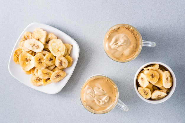 Kwarantanna modna kuchnia. dwie filiżanki z kawą dalgona i chipsami bananowymi na szarym tle. widok z góry
