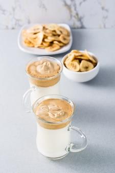Kwarantanna modna kuchnia. dwie filiżanki z kawą dalgona i chipsami bananowymi na szarym tle