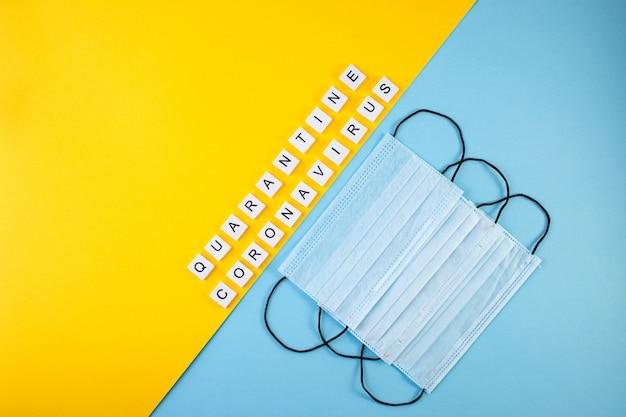 Kwarantanna napisu i koronawirus na niebieskim i żółtym tle. medyczne maski ochronne.