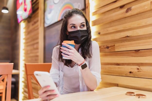 Kwarantanna w kawiarni, młoda kobieta w czarnej masce. wysokiej jakości zdjęcie