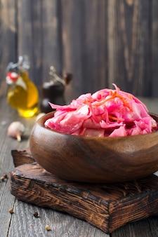 Kwaśna kapusta z burakami i marchewką w bambusowej misce na starym drewnianym stole. styl rustykalny. selektywna ostrość.