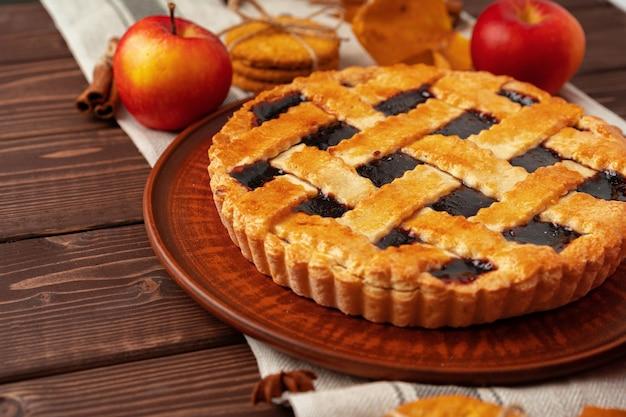 Kwaśne ciasto jagodowe i jabłka na drewnianym stole z bliska