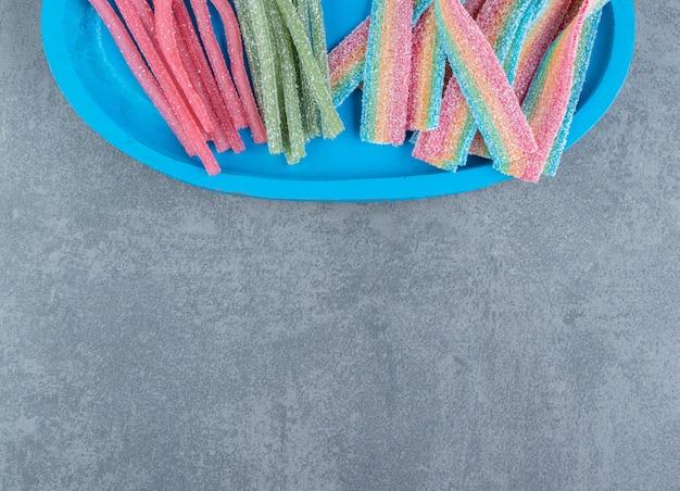 Kwaśne cukierki do żucia na niebieskim talerzu.