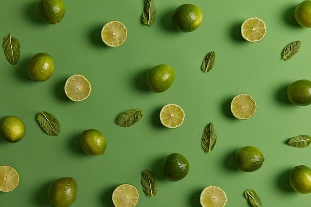 Kwaśne zielone, jasne limonki naładowane substancjami odżywczymi i świeżą miętą na zielonym tle. owoce cytrusowe mogą wzmocnić system odpornościowy, promować zdrową skórę. kwiatowy aromat skórki, składniki cenione na sok