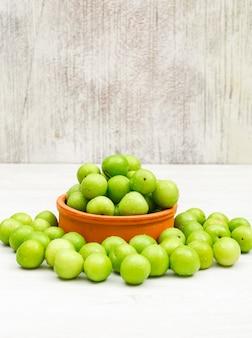 Kwaśne zielone śliwki w okrągłym glinianym pucharze na białej i grunge powierzchni, widok z boku.