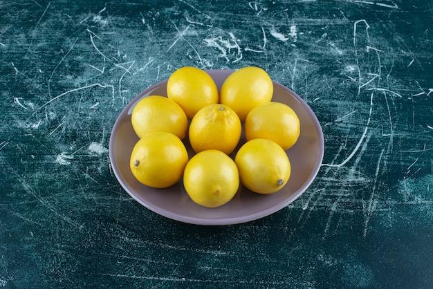 Kwaśne żółte cytryny na fioletowym talerzu.
