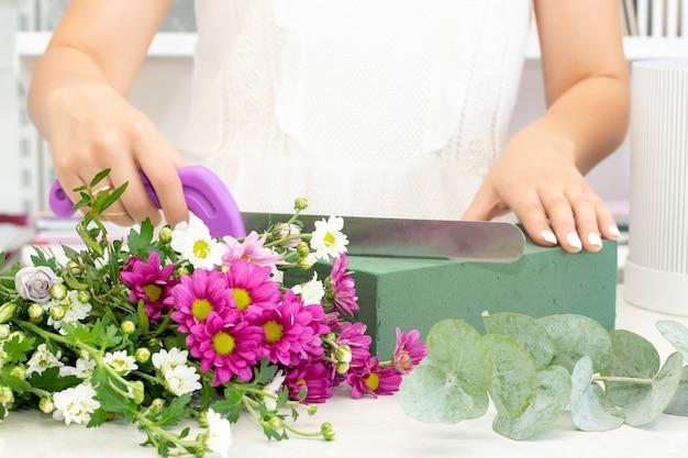 Kwiaciarka dziewczyna pracująca w kwiaciarnidziewczyna kwiaciarni tnie oazę nożem biznes florystyczny kursy florystyczne