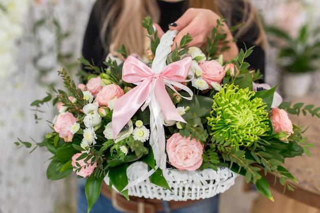 Kwiaciarni kobieta trzyma pięknego bukiet róże w białym koszu