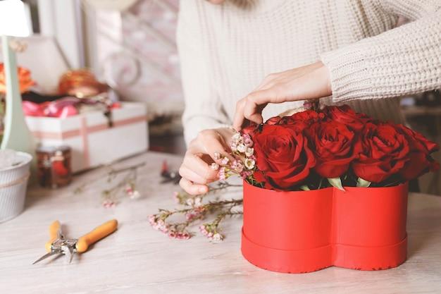 Kwiaciarni kwiaciarni kobieta robi pudełku z czerwonymi różami.