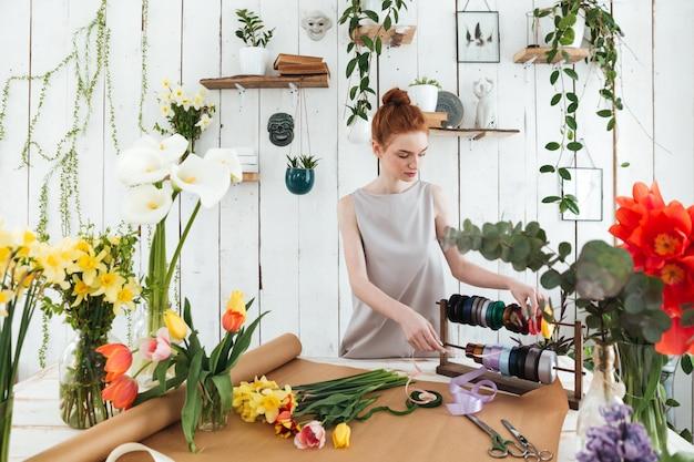 Kwiaciarni młoda kobieta robi bukietowi z kwiatami i faborkami