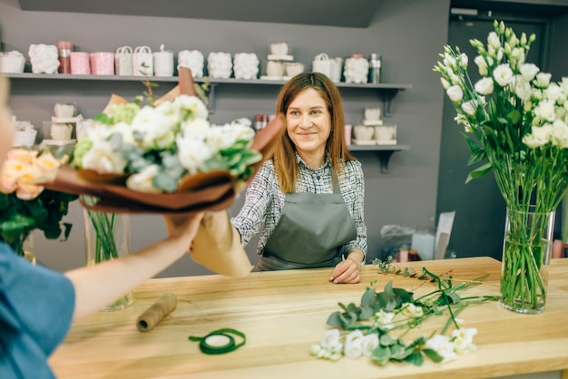 Kwiaciarnia daje klientce świeży bukiet w butiku kwiatowym.