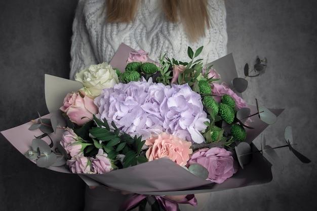 Kwiaciarnia dziewczyna trzyma bukiet luksusowych kwiatów świeżych róż, hortensji, eukaliptusa na tle szarej ściany, selektywna ostrość