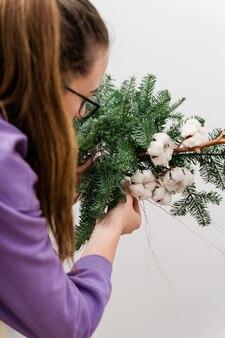 Kwiaciarnia dziewczyna z wiszącą girlandą sosnową. kwiaciarnia kobieta dekorowanie. świąteczna dekoracja diy.