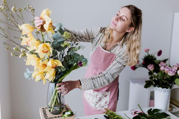 Kwiaciarnia kobieta bierze żółtych kwiaty