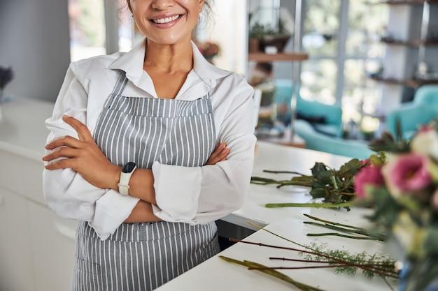Kwiaciarnia kobieta buźka pozuje w studio kwiatowym