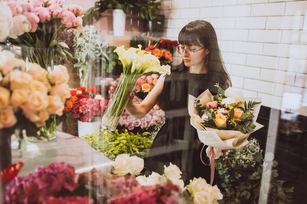 Kwiaciarnia kobieta na jej własny sklep kwiatowy dbanie o kwiaty