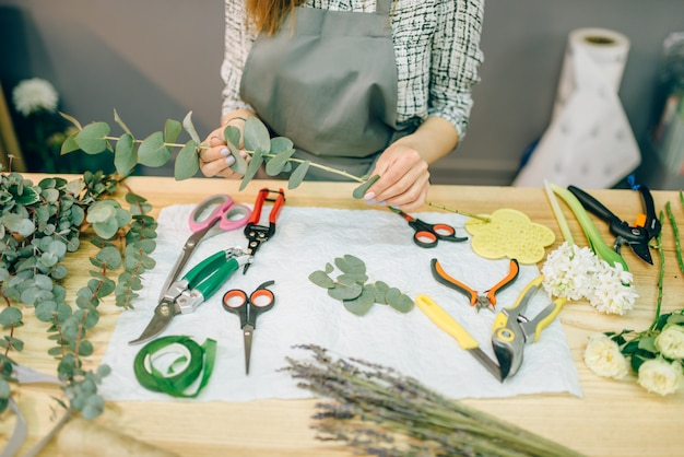 Kwiaciarnia kobieta przygotowuje bukiet róż w miejscu pracy. kwiaciarnia, biznes kwiatowy