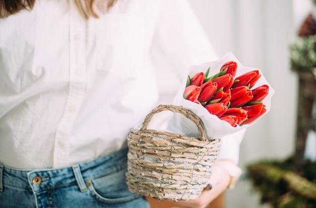 Kwiaciarnia kobieta trzyma kosz z czerwonymi tulipanami w białym papierze. koncepcja dostawy kwiaciarni