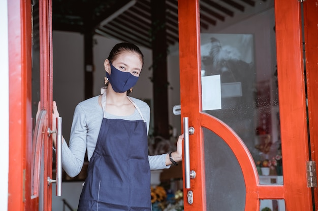 Kwiaciarnia kobieta ubrana w fartuch i maskę na twarz stojąca przy drzwiach kwiaciarni