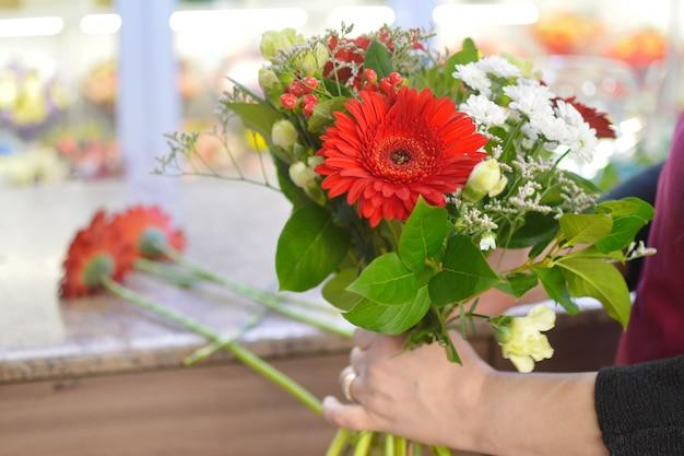 Kwiaciarnia kobieta w pracy. piękna przyjemna praca. kwiaciarnia tworzy kompozycję z kwiatów w pudełku. koncepcja salonu kwiatowego.