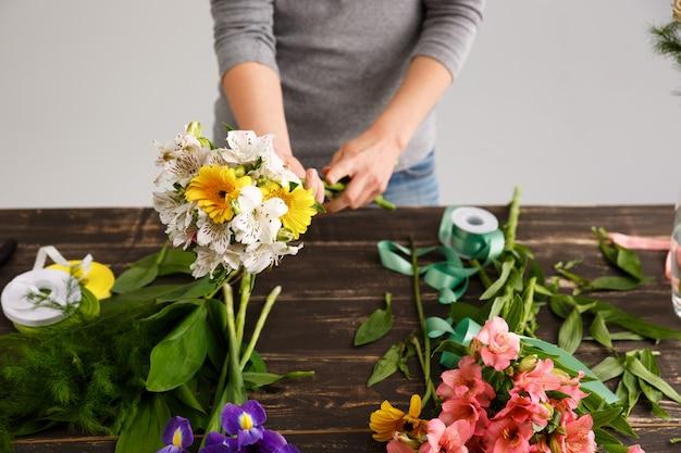 Kwiaciarnia kobieta zrobić bukiet z kolorowych kwiatów