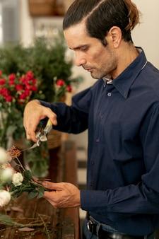 Kwiaciarnia mężczyzna cięcia łodygi kwiatowe na boki
