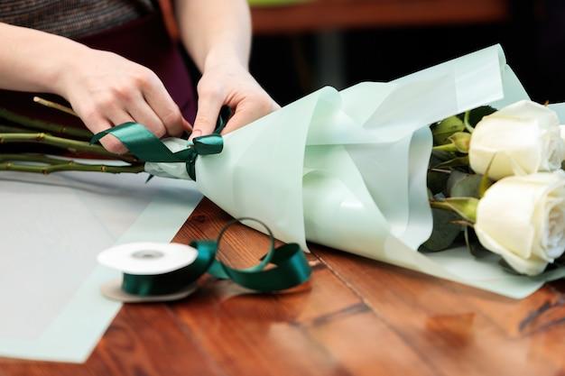 Kwiaciarnia młoda dziewczyna dorosłych sprawia, że bukiet białych róż. zdjęcie ze zbliżeniem.