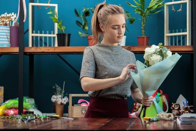 Kwiaciarnia młoda dziewczyna dorosłych sprawia, że bukiet białych róż.