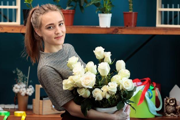 Kwiaciarnia młoda dziewczyna dorosłych trzyma bukiet białych róż i patrzy w kamerę.