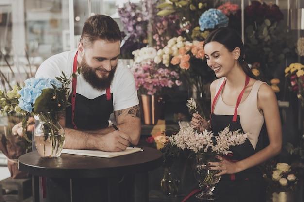 Kwiaciarnia młoda dziewczyna zbiera bukiet kwiatów