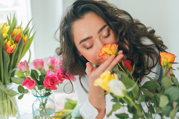Kwiaciarnia młoda kobieta zbiera bukiet kwiatów. wakacje. prezenty. bukiet tulipanów.
