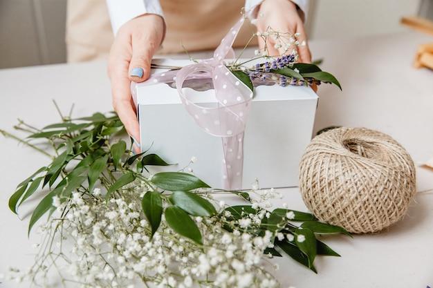 Kwiaciarnia ozdabia pudełko upominkowe kwiatami i wstążką na białym blacie tylko ręce są w ramce
