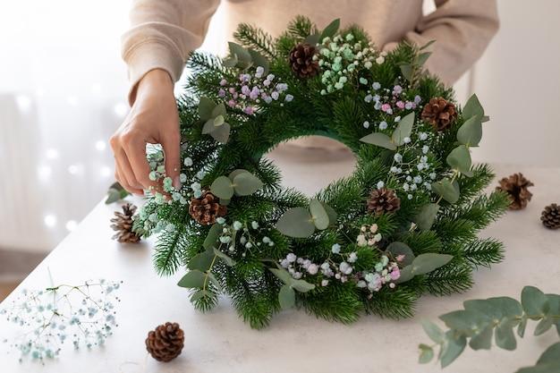 Kwiaciarnia ręce trzymając wieniec bożonarodzeniowy warsztaty wieniec bożonarodzeniowy
