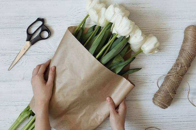 Kwiaciarnia robi bukiet białych tulipanów, widok z góry