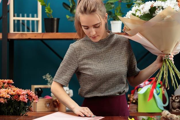 Kwiaciarnia robi bukiet. młoda dorosła dziewczyna trzyma w dłoniach duży bukiet wielobarwnych chryzantem i wybiera papier do dekoracji.