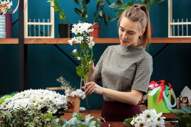 Kwiaciarnia robi bukiet. młoda dorosła dziewczyna wybiera białe chryzantemy na bukiet.